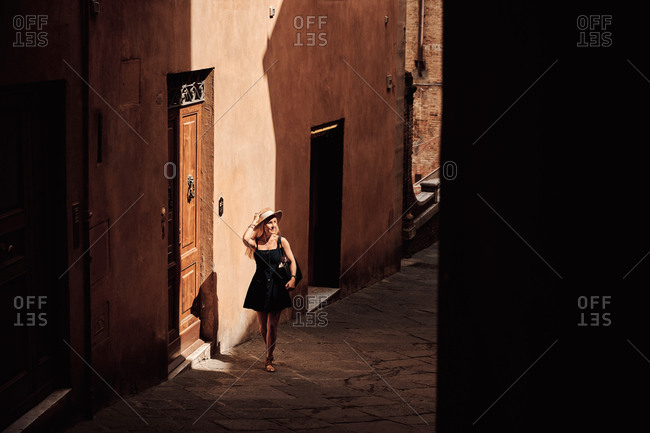 Female tourist walking on narrow street