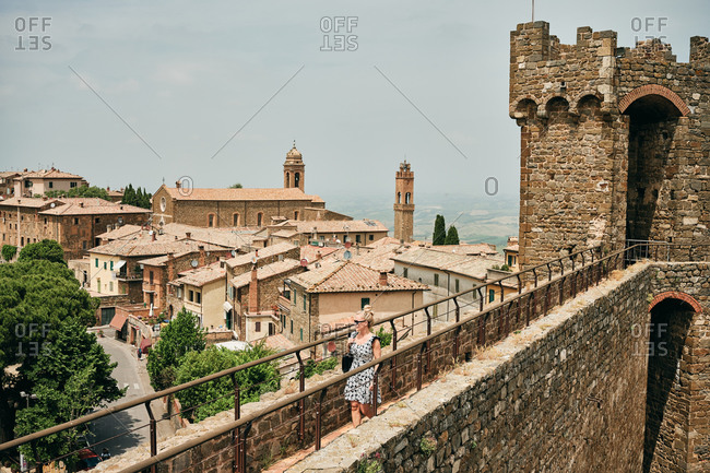 Italy, Tuscany, Montalcino - June 15, 2019: Woman walking on stony wall with observation tower and looking at town