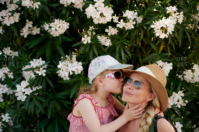 Daughter kissing mother near blooming bush