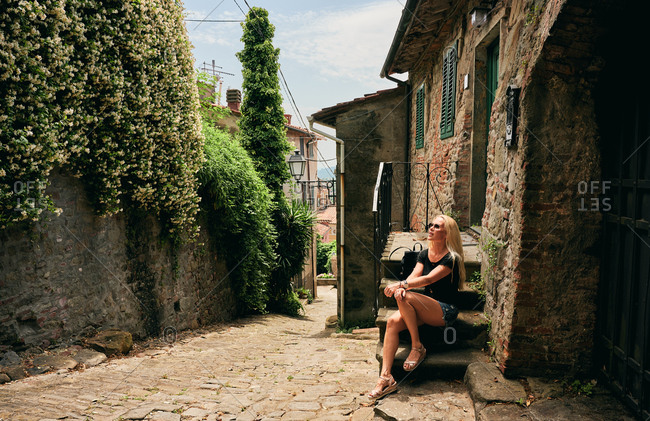 Relaxed woman resting on staircase of aged rural house