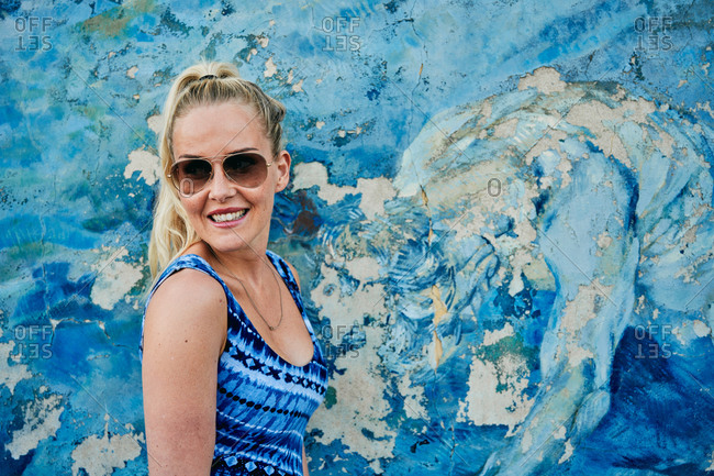 Cheerful woman in sunglasses resting by shabby colorful wall