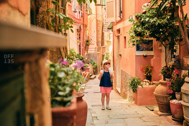 Curious girl in sunglasses walking along scenic European street with plants