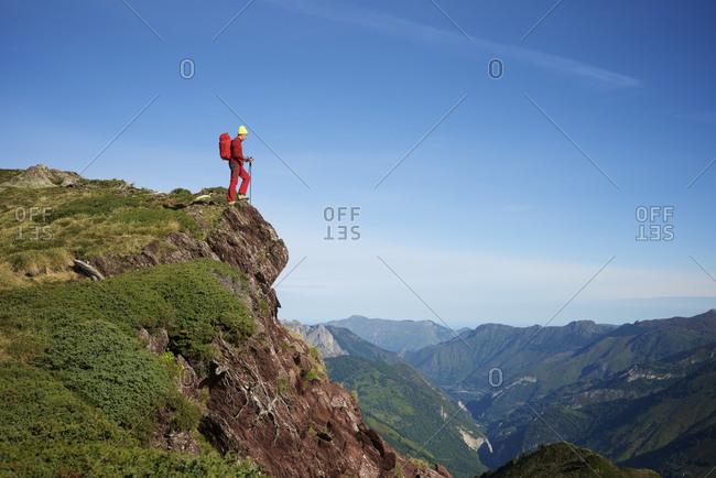Hiker peeking over a cliff.