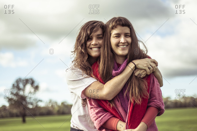 two female friends hug and laugh outdoors on green farm land