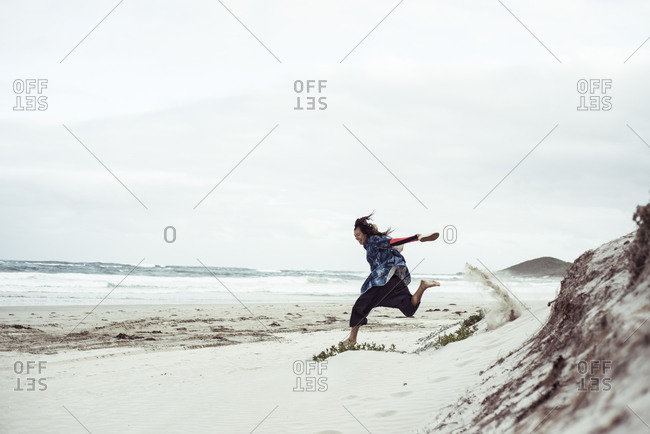 androgynous woman runs and jumps down white sand dune on remote beach