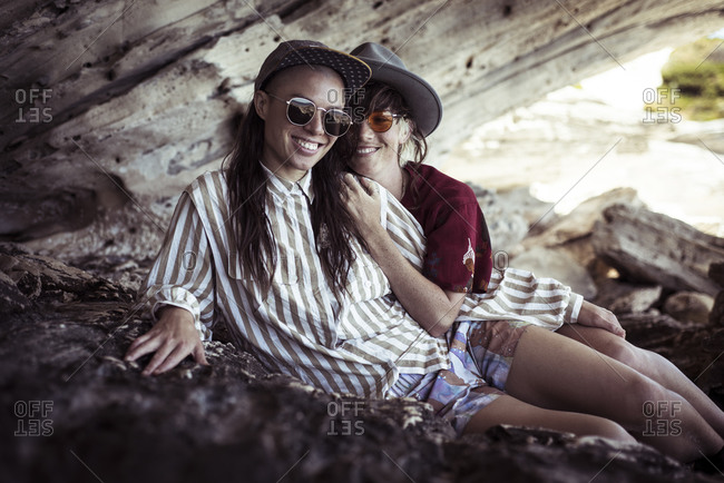 Same sex lesbian couple sit in rocky cliffs on beach holiday in sun