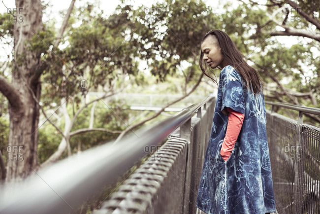 mixed race androgynous woman with blue dress looks out on tree top walk