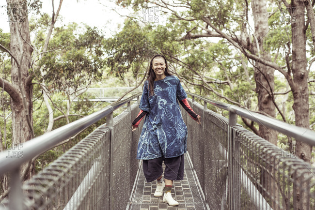 mixed race asian queer woman smiles and laughs on tree top walk