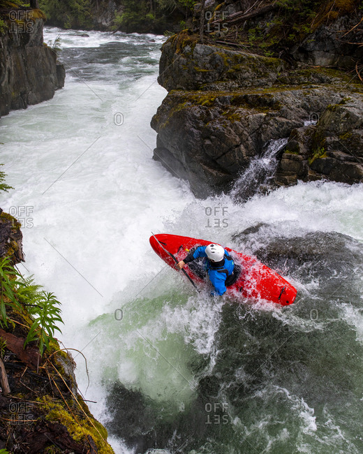 A white water kayaker paddles over a waterfall on the Cheakamus River.