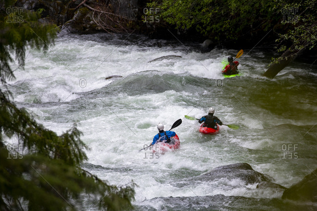 A group of whitewater kayakers paddle down the Cheakamus river.