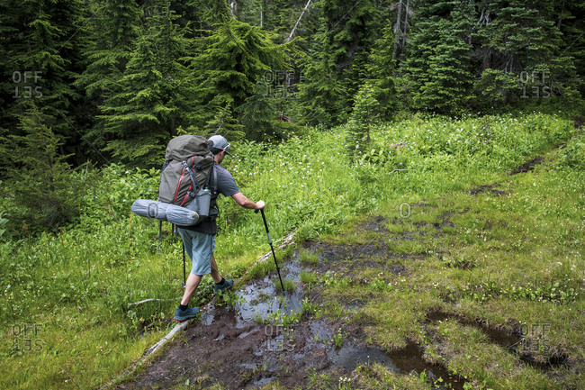 A man hikes along a trail for a weekend camping in the moutains.