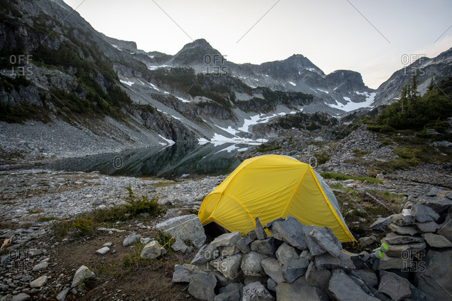 A tent is set up next to an alpine lake and mountains.