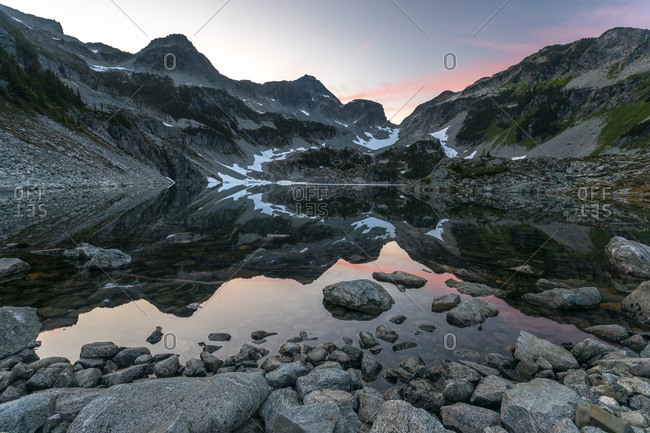 The sun sets over an alpine lake surrounded by mountain peaks.