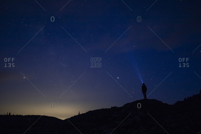 A man stares up at the night sky with a headlamp.