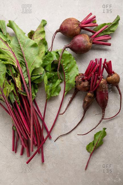 Beetroots and leaves on light surface