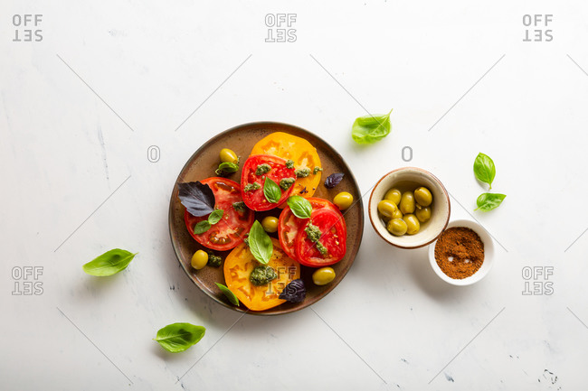 Overhead view of tomato salad on light surface