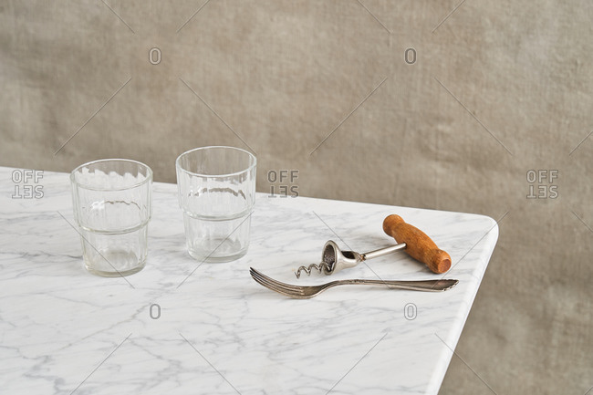 Corkscrew and fork on marble counter by two glasses