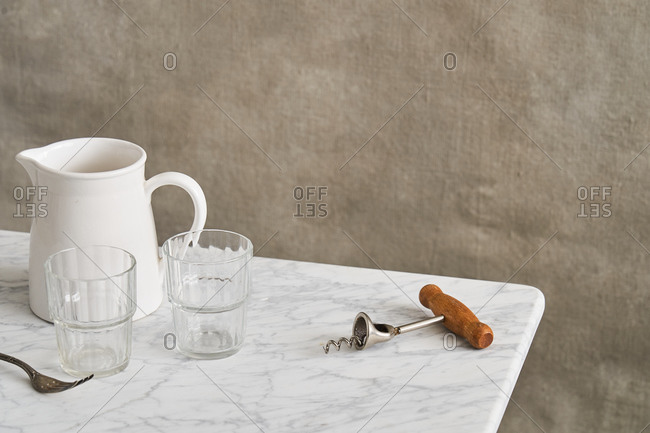 Corkscrew and fork on marble counter by two glasses and a pitcher