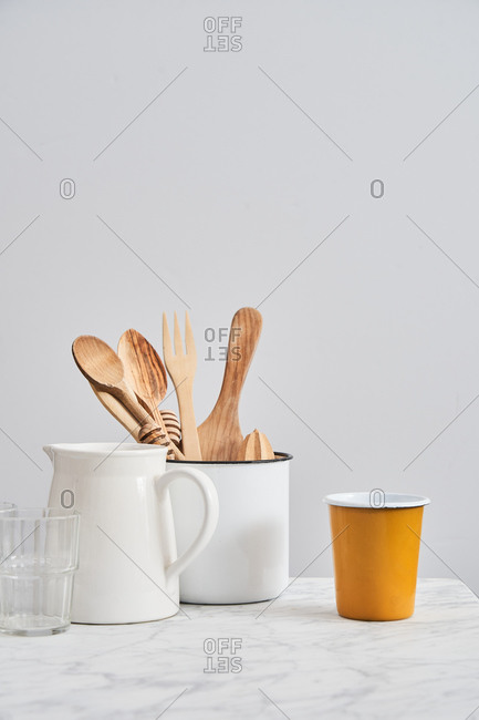 Pitcher and container holding wooden utensils by cups