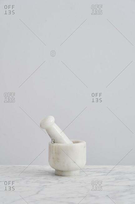 Marble mortar and pestle on kitchen counter with white background