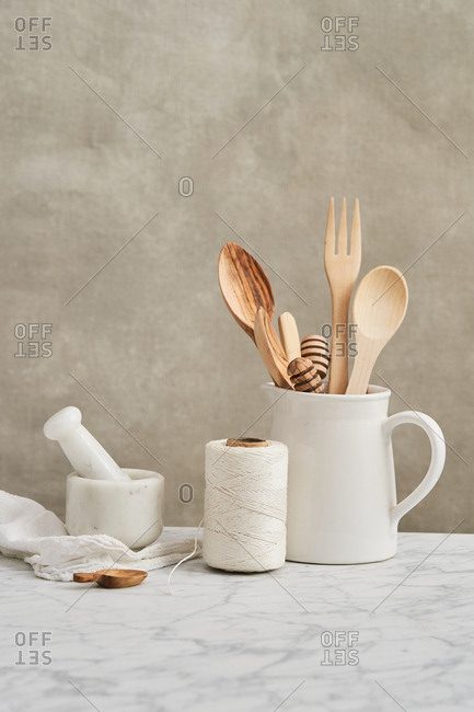 Pitcher holding wooden utensils by mortar, pestle and string