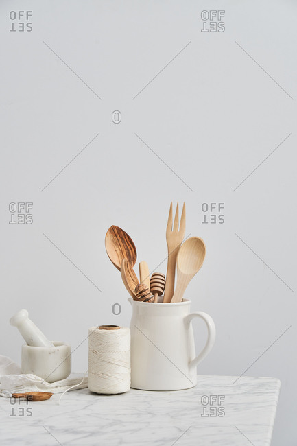 Pitcher holding wooden utensils by mortar, pestle and string with white background