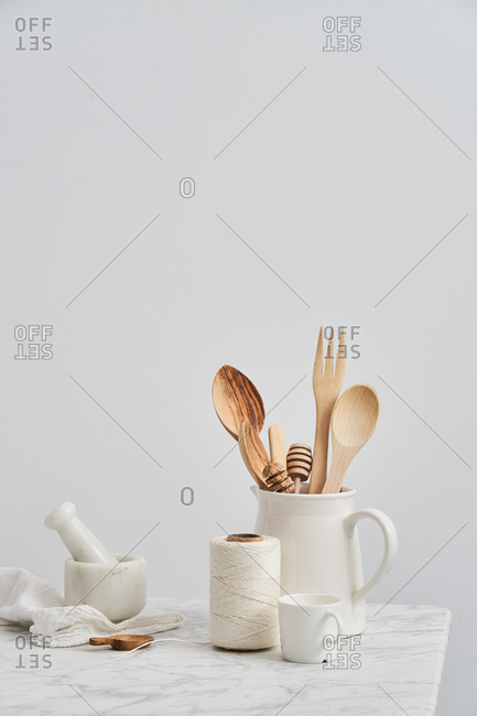 Pitcher holding wooden utensils by mortar, pestle, cup and string with white background