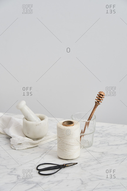 Wooden honey stick in glass by mortar, pestle, string and snips with white background