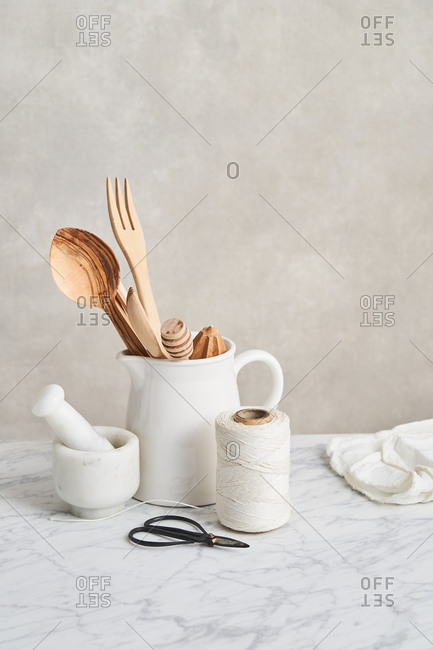 Pitcher holding wooden utensils by mortar, pestle, snips and string