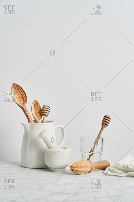 Pitcher holding wooden utensils by mortar, pestle, and reamer with white background