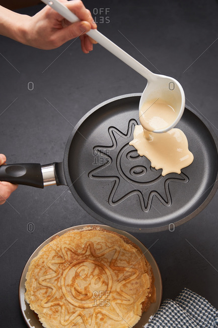 Person preparing thin pancakes with smiley face sun