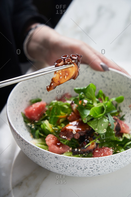 Woman eating a squid with grapefruit salad