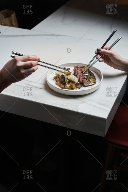 Couple sharing a beef dish with mushrooms using chopsticks