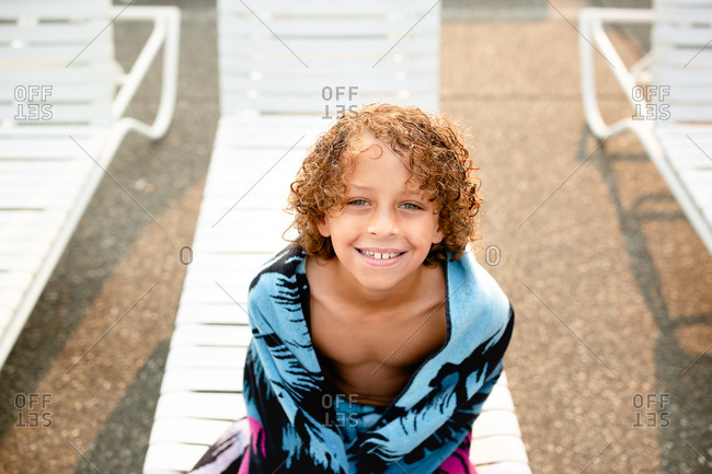 Boy sitting on poolside chair wrapped in a beach towel
