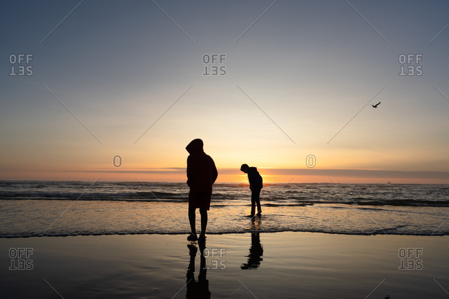 Silhouette of two boys standing in the ocean waves