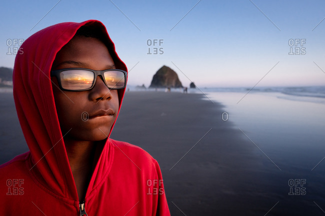 Boy looking out at ocean with sunset reflecting in his glasses on Cannon Beach