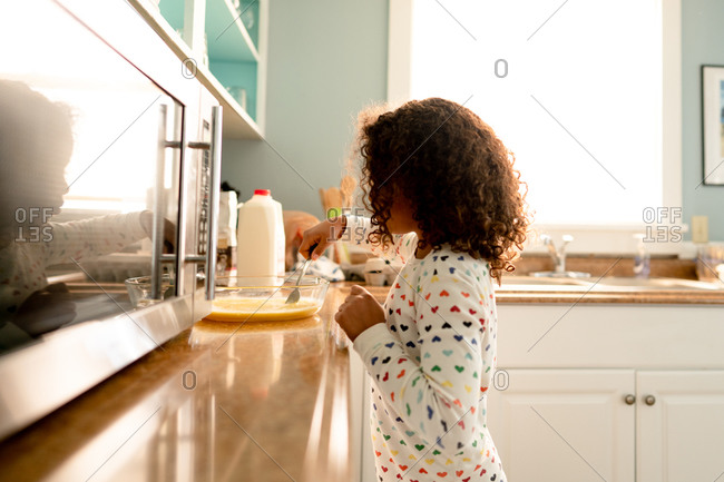 Little girl in kitchen preparing French toast