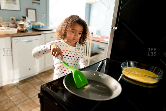 Little girl in kitchen preparing French toast on stove