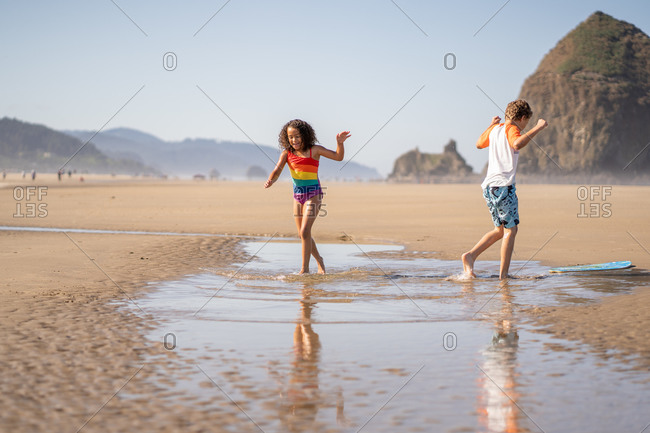 Two kids playing in the tide at Cannon beach