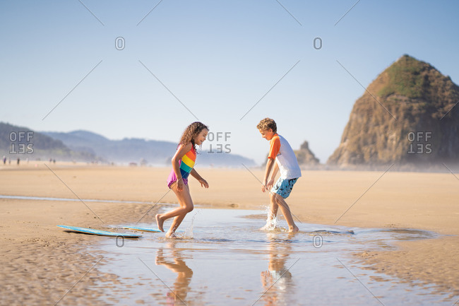 Brother and sister playing in the tide at Cannon beach