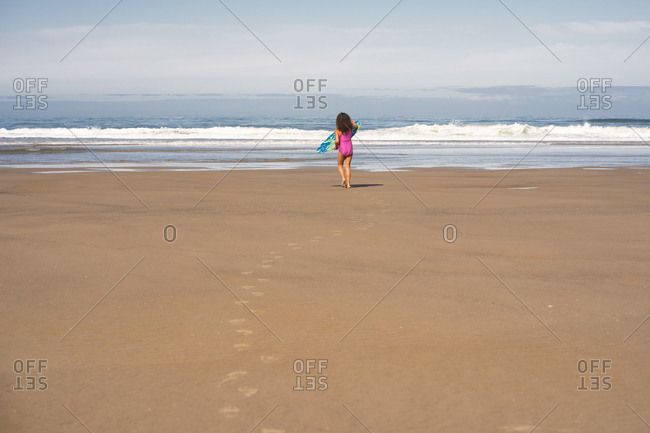 Rear view of girl with boogie board on Cannon beach