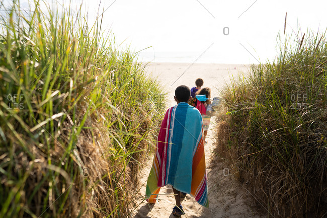 Kids walking on sandy path surrounded by trees