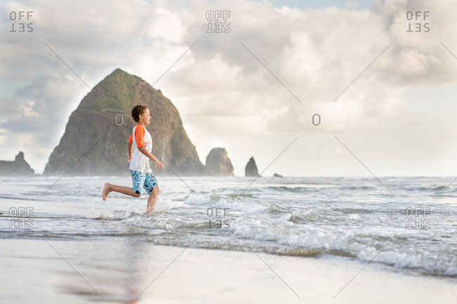Boy running into the waves on Cannon beach