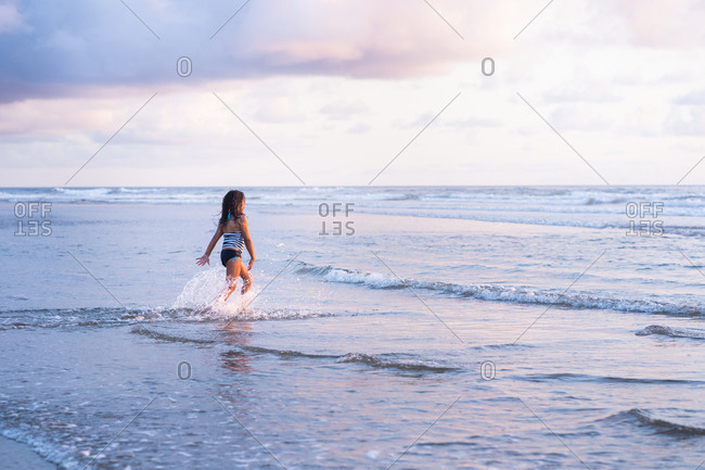 Young girl swimming in the ocean at Cannon beach