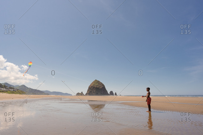 Boy flying kite by Haystack Rock on Cannon beach