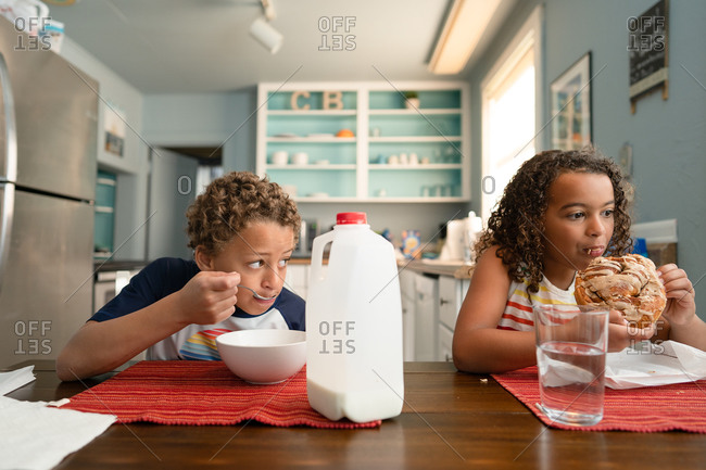 Two kids eating breakfast at dining room table on summer vacation