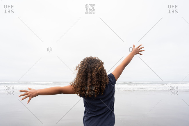 Young girl spreading arms while looking at the ocean on Cannon beach