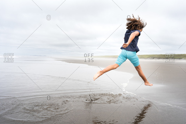 Girl leaping over waves on Cannon beach