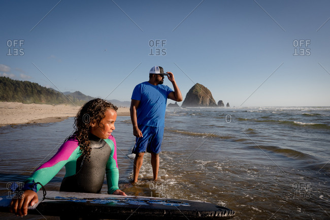 Father in water by young girl with boogie board at Cannon beach