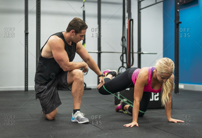 Woman working out with a trainer in a gym